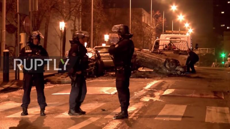 Des policiers sont en observation tandis qu'une voiture, qui a été détruite par les émeutiers dans une banlieue de Paris, est enlevée, le 13 février 2017. (Source de l'image: capture d'écran d'une vidéo Ruptly)