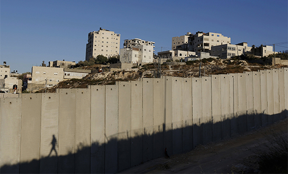 Shuafat refugee camp is seen behind a section of the controversial Israeli barrier near Jerusalem