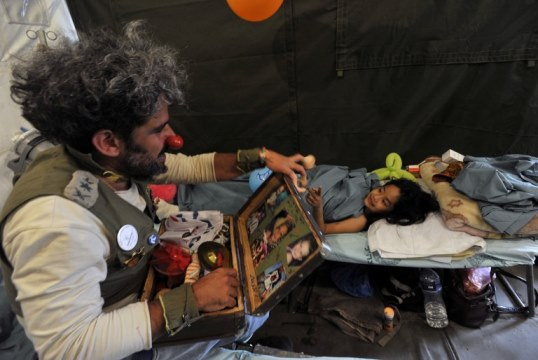 An Israeli medical clown entertains a Nepalese earthquake victim during a visit to a makeshift army camp in Kathmandu on May 6, 2015. The 7.8 magnitude earthquake which struck the Himalayan nation on April 25, 2015, has had a devastating impact on the economy of Nepal where tourism attracted almost 800,000 foreign visitors in 2013 -- many of them climbers heading straight to Mount Everest but also less adventurous tourists seeking the rich cultural history of Kathmandu. AFP PHOTO / PRAKASH MATHEMA