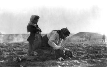 Une femme arménienne agenouillée devant son enfant mort à Alep en Syrie.
