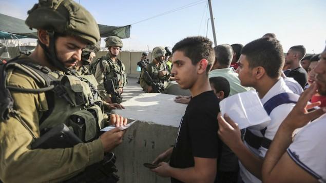Des soldats israéliens contrôlent les cartes d'identité de Palestiniens au checkpoint de Qalandia entre la ville de Ramallah, en Cisjordanie, et Jérusalem, le 1er juillet 2016. (Crédit : Flash90)